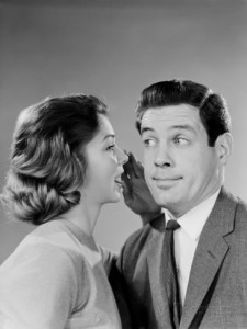 h-armstrong-roberts-woman-whispering-into-man-s-ear-man-pulling-funny-face